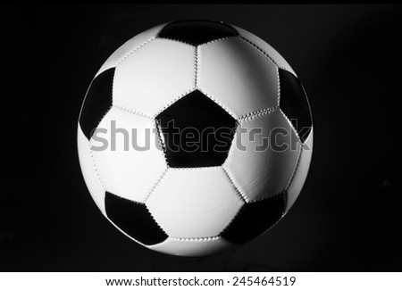 Black and white soccer ball on black background. - stock photo