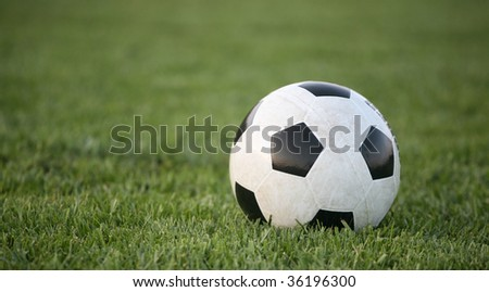 Black and white soccer ball on grass background
