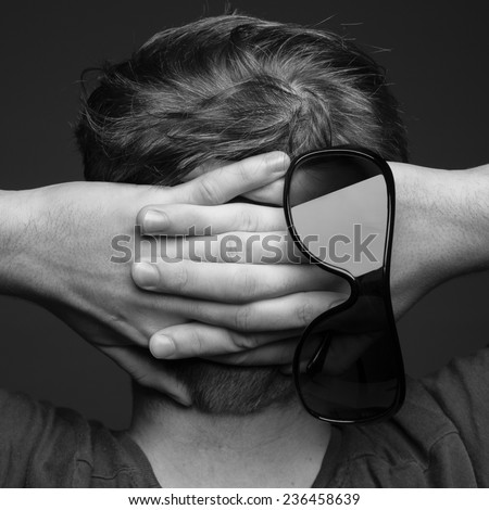 Black and white square image of young male holding hands behind head in a serene like gesture with black sunglasses.  - stock photo