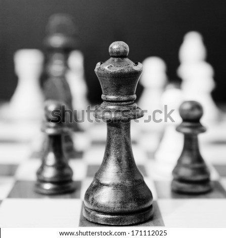 Black and white still life close up detail view of a queen chess dark wooden piece on a chess board while a strategic game is being played. Interior professional strategy game playing. - stock photo