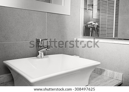 Black and white still life view of a new white sink with silver tap in a stylish bathroom in a quality design home, interior. Bath room and shower in a hotel room, travel and aspirational lifestyle. - stock photo