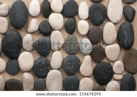 Black and white stones lay in rows on the sand - stock photo