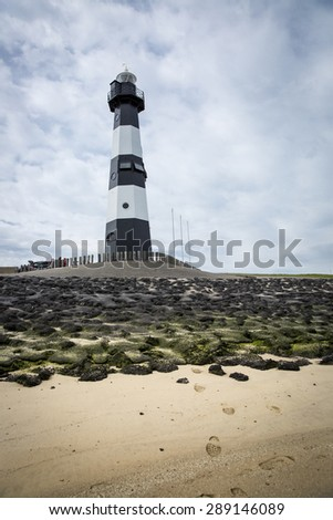 Black and white striped lighthouse, Nieuwe Sluis Breskens, The Netherlands - stock photo
