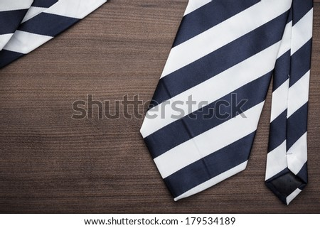 black and white striped necktie on the wooden table - stock photo