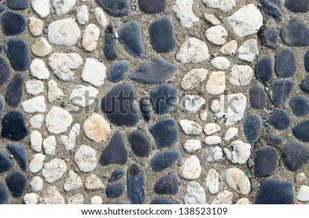 black and white stripes of smooth pebbles set in concrete background - stock photo