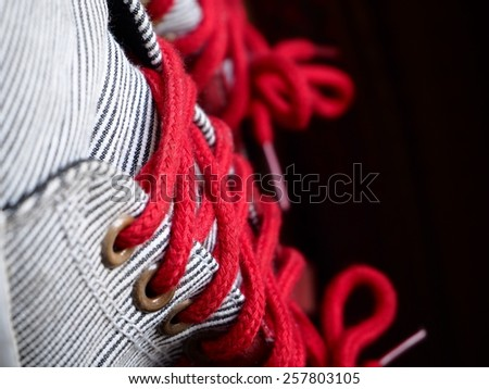 black and white stripped canvas shoes with red lace on dark background. Selective focus. - stock photo