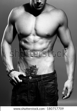 black and white studio shoot of strong athletic man on grey background close up - stock photo