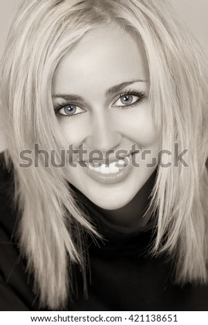 Black and white studio shot of a beautiful happy blond haired blue eyed woman with perfect teeth and smile