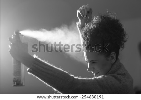 Black and white studio shot of a young girl spraying hairspray and fixing her haircut - stock photo