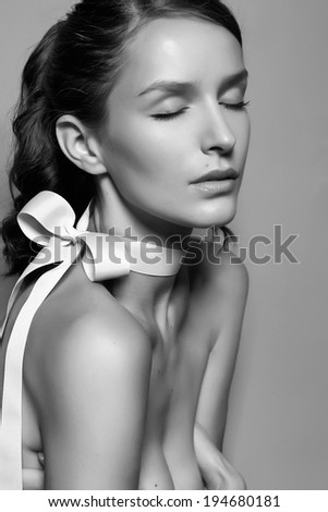 Black and white tender profile fashion portrait of Beautiful gentle young brunette woman with close soft eyes and sensitive mouth wearing silk bow on the neck and right shoulder