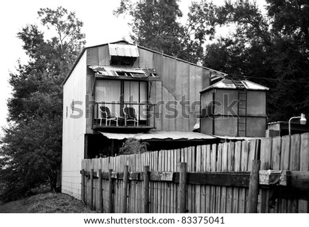 Black and white tin shack with patio chairs - stock photo