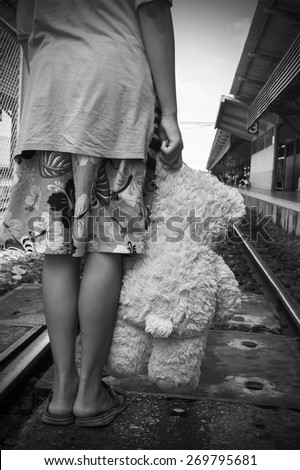 black and white tone girl standing alone and hand hold white bear at Railway Platform - stock photo