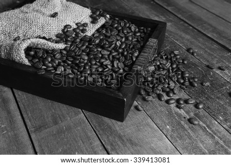 Black and white tone of coffee beans in a sack still life. - stock photo