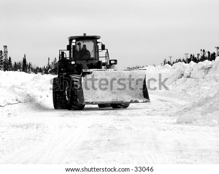 Black and white tractor removing snow from the road in the winter