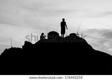Black and white two man fishing on sea shore - stock photo