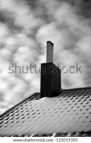 Black and white, vertical photo of the roof covered with snow and chimney under beautiful sky with white clouds - stock photo