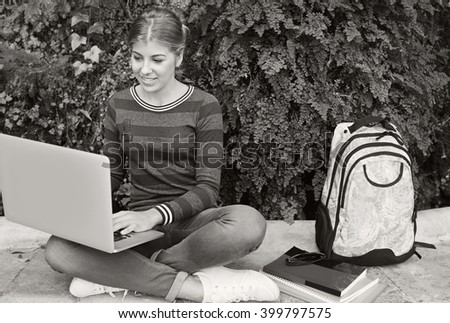 Black and white view of beautiful college student adolescent girl smiling using a laptop computer to study sitting on bench in park with foliage, outdoors. Teenager using technology, lifestyle. - stock photo