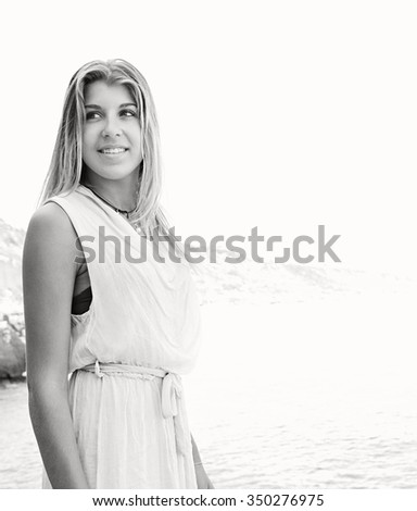 Black and white view of beautiful young adolescent woman on a rocky beach with sunny sky, smiling relaxing and looking away, outdoors. Travel teenager lifestyle and healthy living, nature exterior. - stock photo