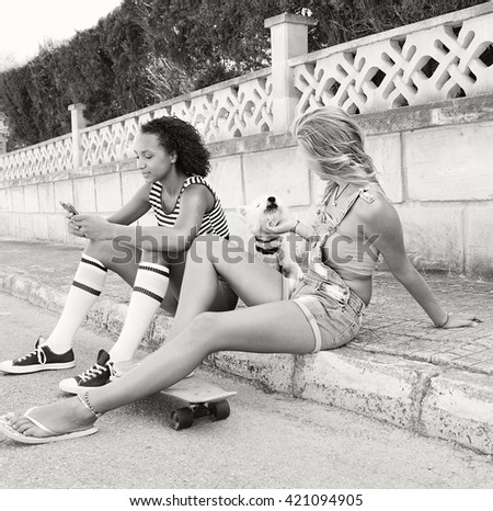 Black and white view of ethnically diverse teenager girls friends together in suburban home exterior with white dog pet, using a smart phone, outdoors. Active adolescent women with animal on holiday. - stock photo