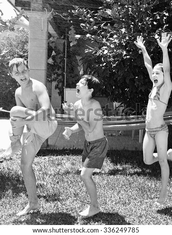 Black and white view of group of friends enjoying a summer party in a home garden, in swimwear with water sprayed on them, fun together outdoors. Kids playing exterior. Active children lifestyle. - stock photo