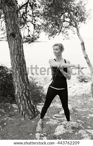 Black and white view of mature healthy woman stretching her arms, exercising in nature with rocks and sea, figure outdoors. Wellness and fitness lifestyle, senior woman athlete discipline and effort.