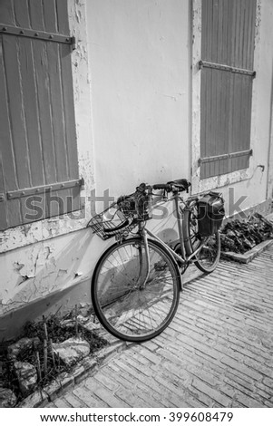 Black and white view of seaside holidays house with wooden shutters with a bike in front - stock photo