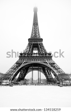 Black and white view of the Eiffel tower in winter under the snow.