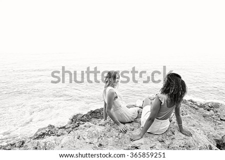 Black and white view of two diverse friends, caucasian and african american teenager girls relaxing together on rocks, smiling by the sea, outdoors nature. Holiday travel lifestyle, beach exterior. - stock photo
