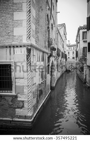 Black and white view of typical little venetian romantic canal in the mist, Venice, Italy