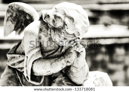 Black and white vintage image of a sad mourning angel on a cemetery with a diffused background - stock photo