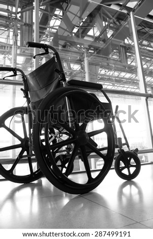 Black and white Wheelchair service in airport terminal - stock photo