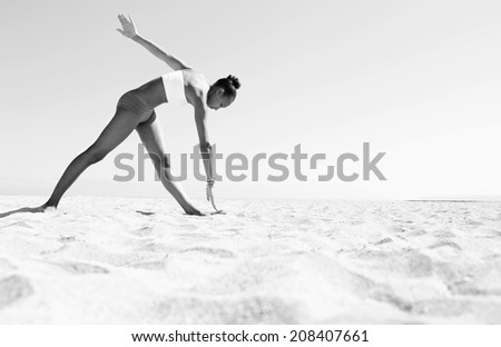 Black and white wide view of an athletic african american young woman exercising stretching her arms and legs against a blue sky on a sunny beach. Sport and healthy lifestyle, outdoors. - stock photo