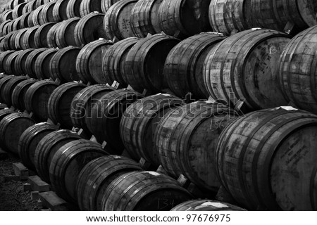 Black and white Wine barrels stacked in the old cellar of the winery. - stock photo