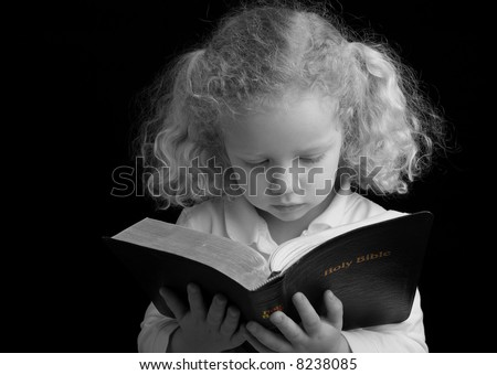 Black and white (with color accent) image of a child reading the Holy Bible. - stock photo