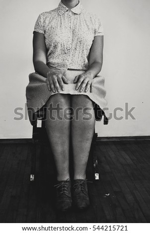 Black and white woman sitting on a chair
