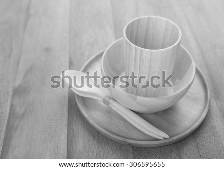 Black and white wood kitchen utensils over grunge wooden table background 