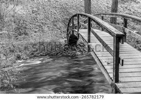 Black and White wooden bridge over a soothing river
