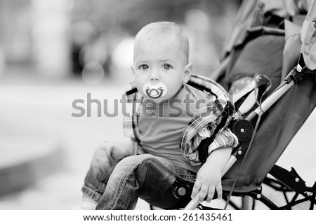 Black and white, 1 year baby sitting in the baby carriage, with a pacifier in his mouth, blond hair, plaid shirt, jeans, a city on the background of trees. Baby with a pacifier. - stock photo
