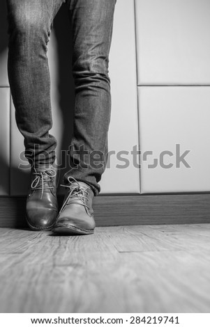 Black and White  Young fashion man's legs in blue jeans and brown boots on wooden floor