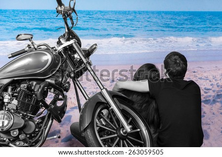 Black and White Young Romantic Couple Sitting next to Motorcycle on Color Sandy Beach Admiring Waves on Shore - stock photo