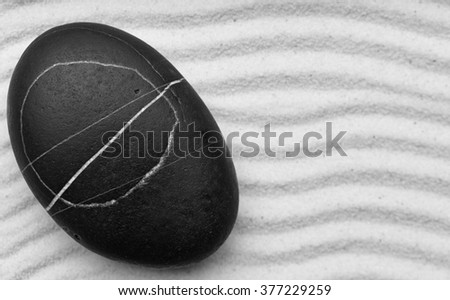 Black and white zen garden with a wave lines in the sand with big stone