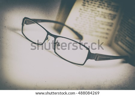 Black and whiteglasses and book vintage blur dust and scratch filter
