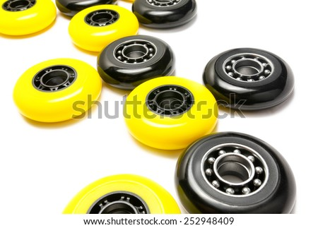 Black and yellow color inline skate wheels laying in random order on white background - stock photo