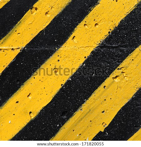 Black and yellow striped caution pattern on concrete wall