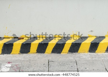 Black and yellow traffic sign on road border