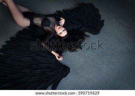 Black angel lying on the floor. Sensual woman - stock photo
