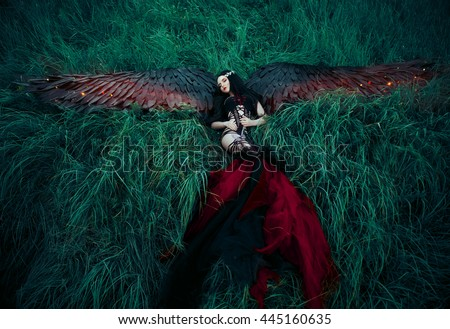 Black Angel. Pretty girl-demon with black wings. An image for Halloween. Image of an old book of fairy tales. Fashionable toning creative computer colors - stock photo