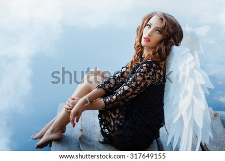 Black angel with white wings. Her eyes were terrible and light. See more photos of this series. - stock photo