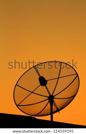 Black antenna communication satellite dish in sunset sky - stock photo