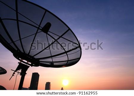 black antenna communication satellite dish over sunset sky in cityscape - stock photo